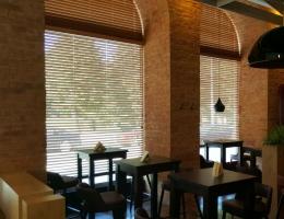 Полукруглые деревянные жалюзи украшают окна кафе в Латвии