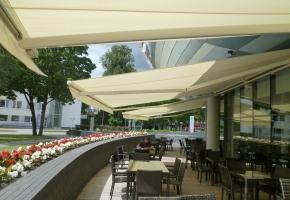 Minimalistinės ir vienspalvės markizės puikiai dera su moderniu, išskirtinės formos pastato fasadu